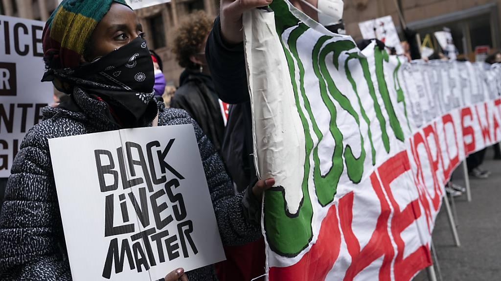 Demonstranten gehen in Minneapolis mit Transparenten und Plakaten auf die Straße, während im Mordprozess gegen den ehemaligen Polizisten Derek Chauvin wegen der Tötung von George Floyd verhandelt wird. Foto: John Minchillo/AP/dpa