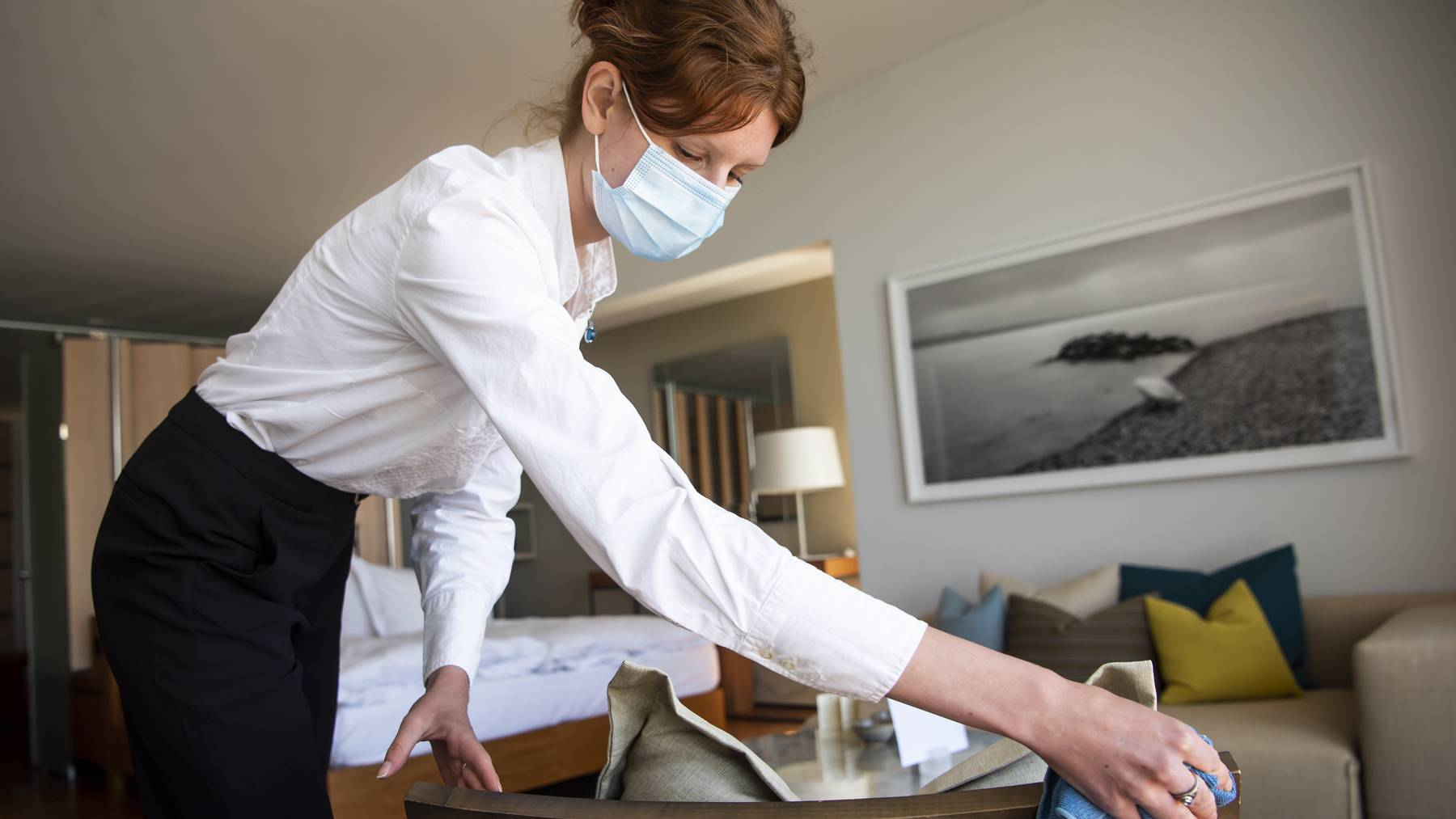 Eine Angestellte inspiziert ein Zimmer eines Hotels beim Neuenburgersee.