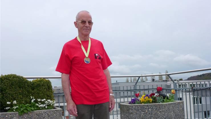 James Anneler posiert auf seinem Balkon in Urdorf mit der Medaille vom Zürich Marathon. yst