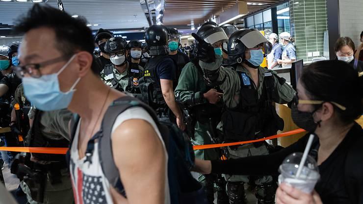 Polizisten und mutmassliche Demonstranten in einem Einkaufszentrum in Hongkong.