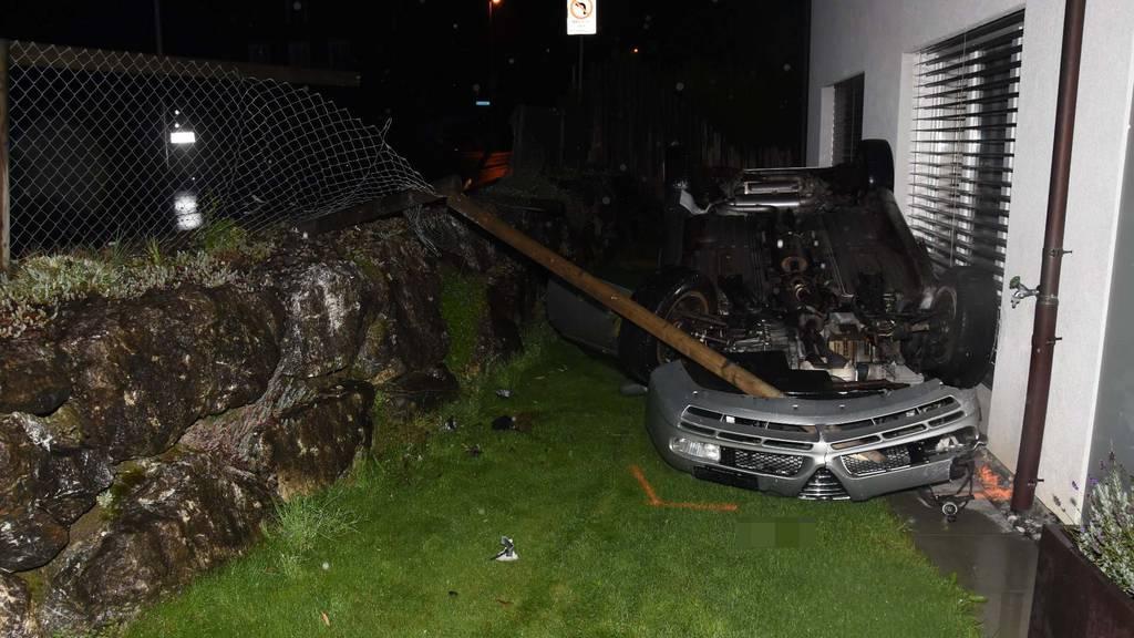 Mann «parkiert» Auto auf dem Dach liegend in Garten