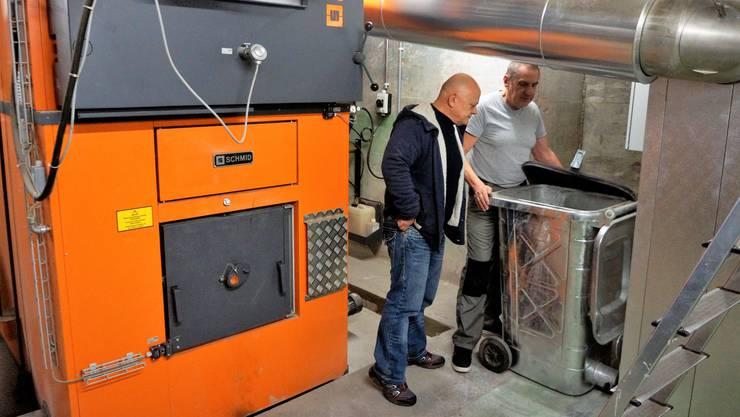 Beat Kohler, Gemeinderat und Mitglied der Umweltkommission, und Karl von Burg, zuständig für die Schnitzelheizung, begutachten die Tonne mit dem Filterstaub aus der Schnitzelheizung in der Fernwärmezentrale.