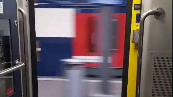 Ein Zug fährt mit offener Türe von Brugg nach Baden