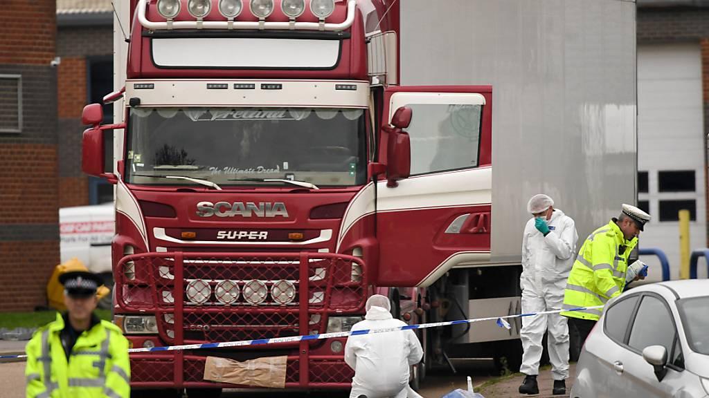 ARCHIV - Polizisten und Mitarbeiter der Spurensicherung arbeiten an dem LKW, in dem 39 Leichen gefunden wurden. Foto: Stefan Rousseau/PA Wire/dpa