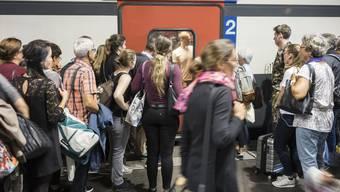 Passagiere warten auf einem Perron am Bahnhof Bern, bis sich die Türen eines Intercitys öffnen.