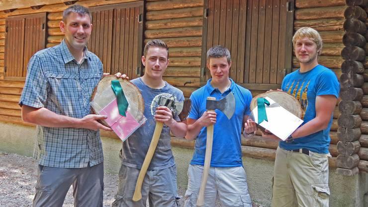 """Die beiden Ausbilder Ruedi Graf (links) und Lorenz Jud (rechts) übergaben Daniel Schmutz (links, mit Ehrenaxt) und Beni Geissmann (rechts, mit """"Axt zum arbeiten"""") auf einer Holzscheibe den Fähigkeitsausweis als Forstwart."""