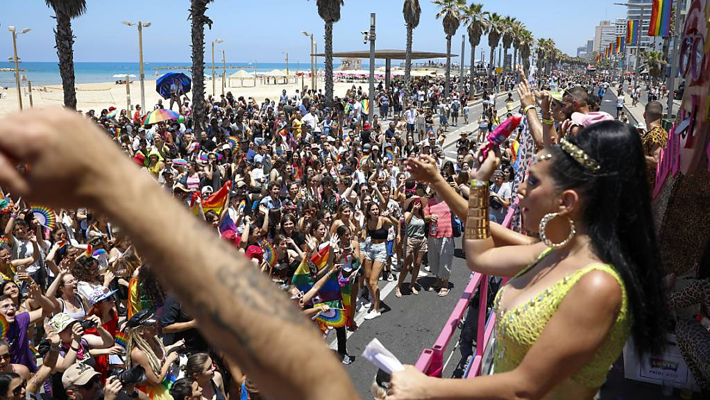 Teilnehmende winken bei der jährlichen Pride Parade von einem fahrenden Wagen aus den Zuschauerinnen und Zuschauern zu. Zehntausende haben bei der Gay-Pride-Parade in Tel Aviv gefeiert und gleiche Rechte für Schwule, Lesben, Bi- und Transsexuelle (LGBTQIA+) gefordert. Foto: Ariel Schalit/AP/dpa