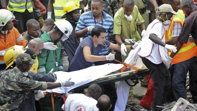 Mitarbeiter des Roten Kreuzes tragen einen Leichnam weg