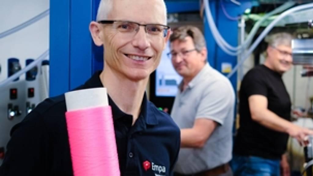Robert Hufenus vor der Maschine, die als Weltneuheit Übertragungskabel mit Flüssigkern herstellt. Die Spule, die er in der Hand hält, ist nicht nur rosa, damit sie schick aussieht: Die Farbe erlaubt, die Dehnung der Faser zu messen. Das erweitert die Einsatzmöglichkeiten erheblich. (Pressebild)