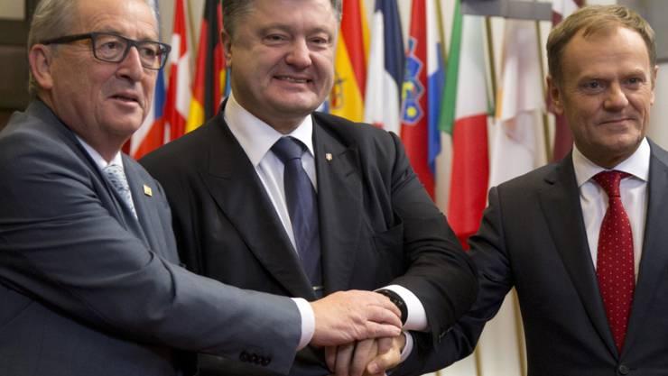Der ukrainische Präsident Poroschenko (M) mit EU-Kommissionspräsident Juncker (l) und EU-Ratspräsident Tusk