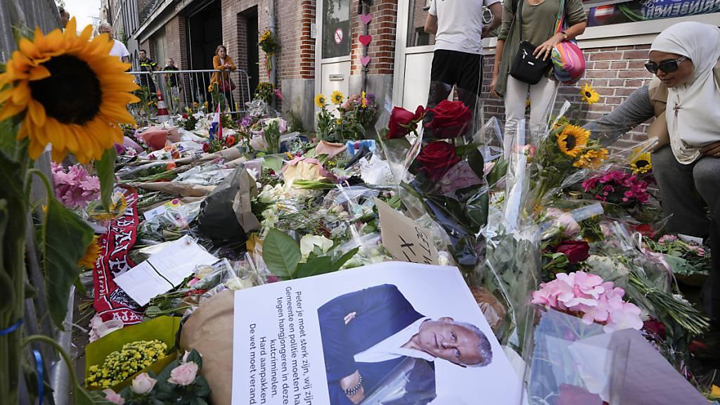 Menschen haben Bilder des Kriminalreporters Peter R. de Vries und Blumen am Tatort in Amsterdam niedergelegt. Der prominente Journalist ist nach dem Mordanschlag seinen schweren Verletzungen erlegen. Foto: Peter Dejong/AP/dpa