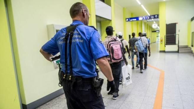 Ein Grenzwächter in Chiasso begleitet Flüchtlinge zur Personenkontrolle