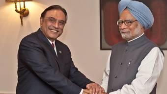 Der pakistanische Präsident Asif Ali Zardari (l.) hält die Hände des indischen Premiers Manmohan Singh in Neu Delhi