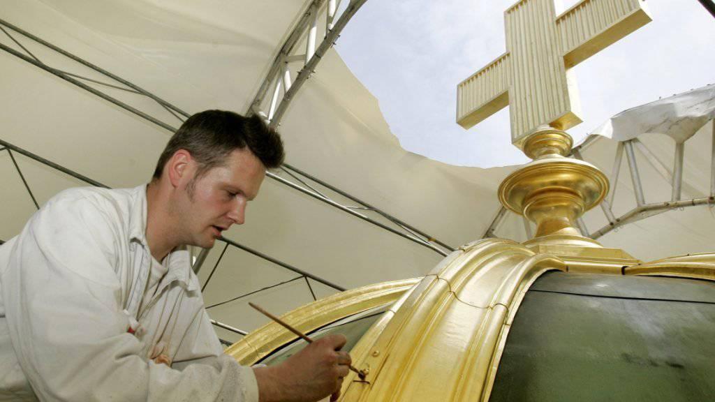 Das mit Gold verzierte Kreuz auf der Kuppel des Bundeshauses während der Renovation 2007. (Archivbild)