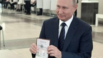 Wladimir Putin, Präsident von Russland, zeigt einer Mitarbeiterin der Wahlkommission seinen Pass in einem Wahllokal. Foto: Alexei Druzhinin/Pool Sputnik Kremlin/AP/dpa