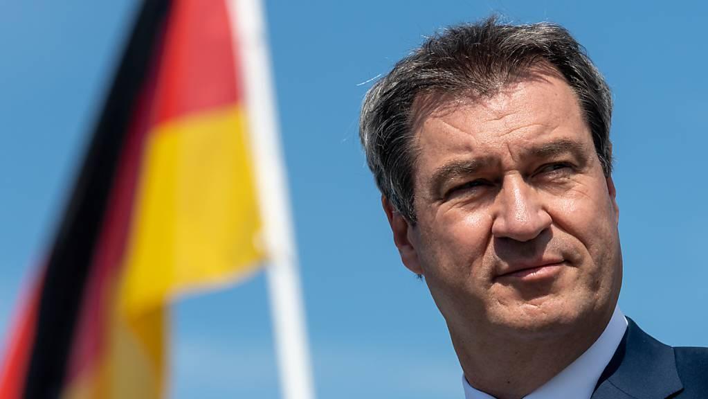 Markus Söder (CSU), Ministerpräsident von Bayern, steht vor der Abfahrt mit einem Schiff der Chiemsee-Schifffahrt auf die Insel Herrenchiemsee vor einer deutschen Flagge. (Archivbild) Foto: Peter Kneffel/dpa/Pool/dpa
