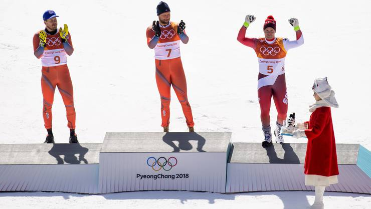 Silver medal, Kjetil Jansrud of Norway, left, Gold medal, Aksel Lund Svindal of Norway, and Bronze medal, Beat Feuz of Switzerland, right, celebrate in the finish area on the podium during the men Alpine Skiing downhill race in the Jeongseon Alpine Center during the XXIII Winter Olympics 2018 in Pyeongchang, South Korea, on Thursday, February 15, 2018. (KEYSTONE/Jean-Christophe Bott)