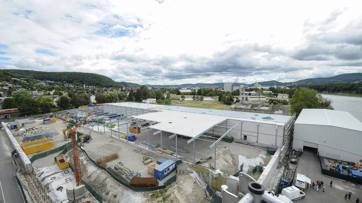 Die Hallen, in denen der belastete Boden bis zu 26 Meter Tiefe ausgetauscht wird, sind derzeit im Bau. Die Halle ganz rechts am Rheinufer beherbergt die Grundwasser-Reinigungsanlage.
