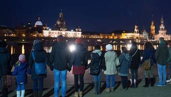 Dresdner formen eine Menschenkette zur Erinnerung an die Zerstörung ihrer Stadt vor 71 Jahren und an die Zehntausenden von durch Brandbomben der Alliierten verkohlten Menschen.