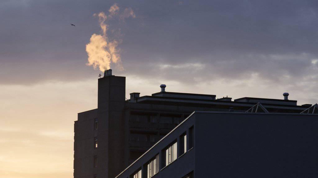 Rauch steigt aus Schornsteinen auf Hausdächern von Zürich Albisrieden. (Symbolbild)