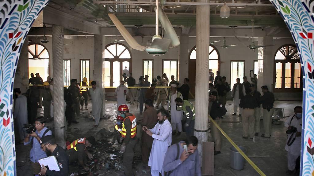 Rettungshelfer und Polizisten inspizieren den Ort in einer Koranschule, in der eine Explosion stattgefunden hat. Dabei sollen auch Kinder getötet und viele weitere Menschen verletzt worden sein.
