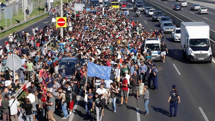 Nachdem ihnen die Reise mit dem Zug verwehrt wurde, nehmen Flüchtlinge den langen Marsch von Budapest Richtung Wien in Angriff.Frank Augstein/ap/keystone