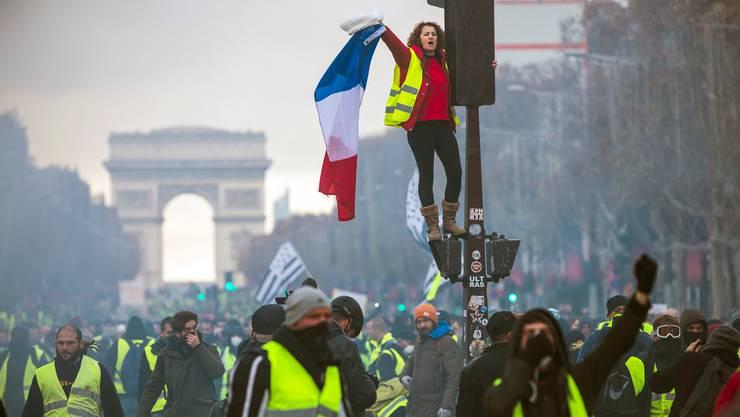 Mit gelben Westen und Nationalflagge auf den Champs-Élysées gegen höhere Benzinpreise: Die Protestbewegung wird für Macron gefährlich.