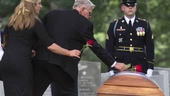 Beisetzungsfeiern auf dem Militärfriedhof Arlington. Trauernde legen Rosen auf den Sarg von John Herb.
