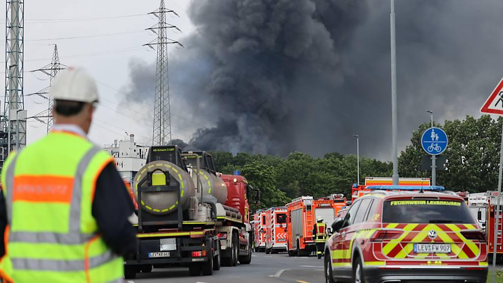 dpatopbilder - Einsatzfahrzeuge der Feuerwehr stehen unweit einer Zufahrt zum Chempark über dem eine dunkle Rauchwolke aufsteigt. Foto: Oliver Berg/dpa