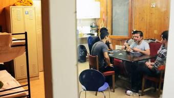 Asylunterkunft, im Spiegel junge Männer aus Afghanistan, die sich die Zeit beim Kartenspiel vertreiben.