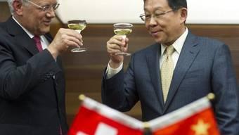 Bundesrat Johann Schneider-Ammann (l.) stösst mit dem chinesischen Handelsminister Chen Deming an