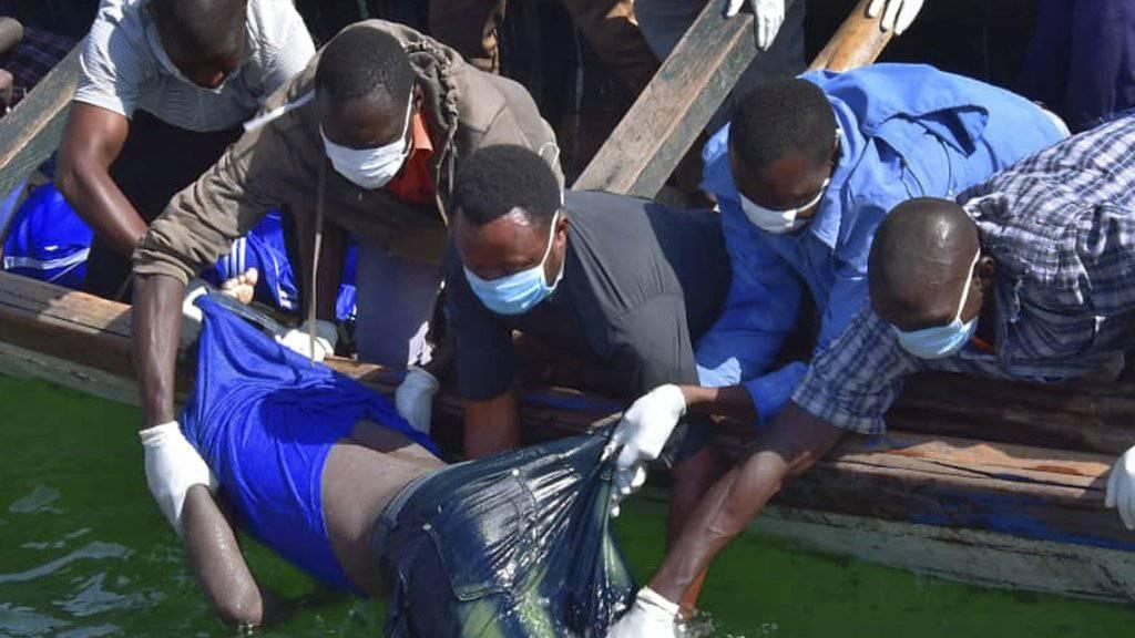 Rettungskräfte ziehen nach dem Fährunglück auf dem Victoriasee einen ertrunkenen Passagier aus dem Wasser.