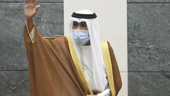 Scheich Nawaf Al Ahmad Al Sabah mit Mund-Nasen-Schutz, der neue Emir von Kuwait, winkt, nachdem er den Verfassungseid vor der Nationalversammlung geleistet hat. Foto: Jaber Abdulkhaleg/AP/dpa