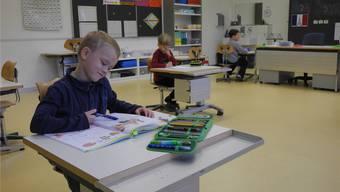 Ein Zuzger Erstklässler löst selbstständig einfache Subtraktions-Aufgaben, während im Hintergrund zwei weitere Schüler unterschiedliche Lernkontrollen schreiben. Marc Fischer