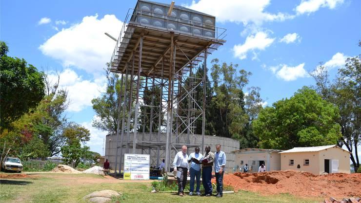 Corrado Minikus (rechts) mit Vertretern der lokalen Behörden vor dem Wasserturm. Das vom Fluss kommende Wasser fliesst in den runden Behälter und wird von dort in den Tank auf dem Gestell gepumpt.zvg