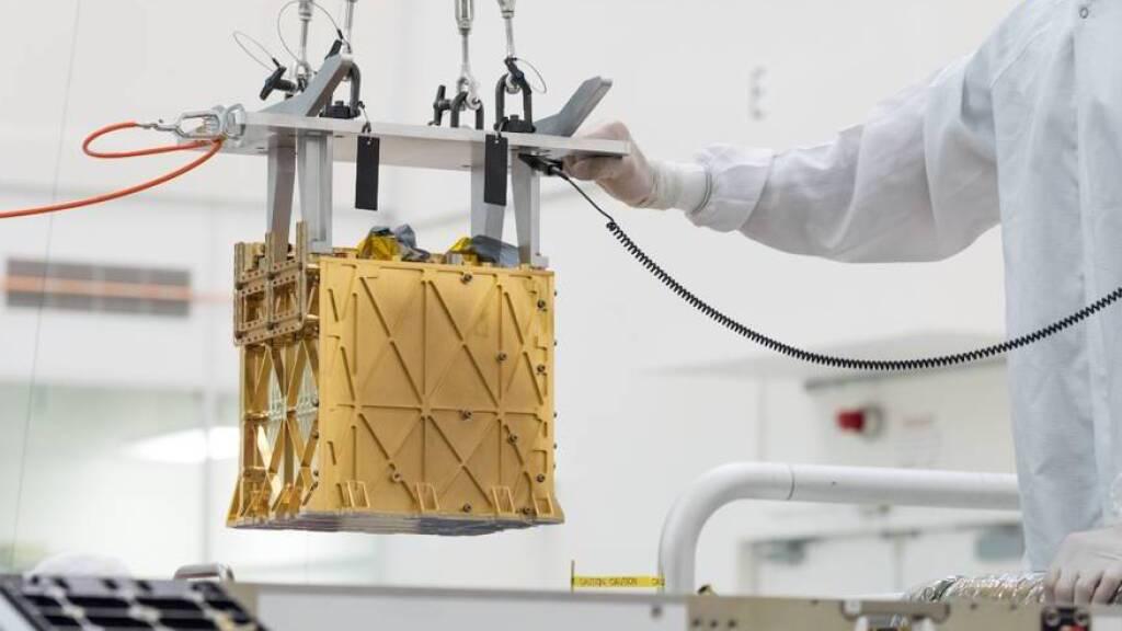 HANDOUT - Techniker in einem Nasa-Labor führen das wissenschaftliche Gerät namens «Moxie» in das Innere des Mars-Rover «Perseverance» ein. Foto: -/Nasa/JPL-Caltech/dpa - ACHTUNG: Nur zur redaktionellen Verwendung und nur mit vollständiger Nennung des vorstehenden Credits