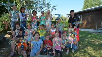 Die Kinder präsentieren mit Betreuerin Sandra Fluri ihre aus PET-Flaschen hergestellten Windräder.