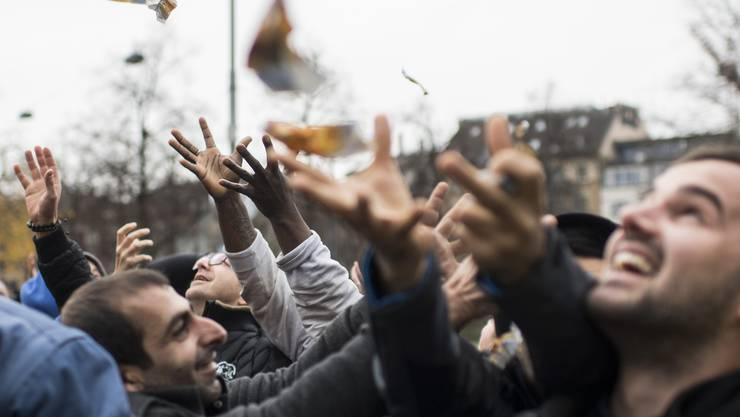 """Menschen versuchen gierig das Geld von Aktionist Joachim Ackva auf dem Helvetiaplatz zu fangen, aufgenommen am Montag, 21. November 2016 in Zuerich. Der Finanzberater Joachim Ackva laesst 10-Franken Scheine auf belebte Plaetze regenen, und will mit der Aktion auf seine Idee des """"Weltkontos"""" aufmerksam machen. Jeder Buerger soll freiwillig ein Tausendstel seines Vermoegens auf ein Weltkonto einzahlen, das bei den Vereinten Nationen angesiedelt ist. Bei einem Vermoegen von 100.000 Euro waeren das 100 Euro. Mit dem Geld sollen die 17 globalen Entwicklungsziele umgesetzt werden, die die 150 Staats- und Regierungschefs im September bei der UN-Vollversammlung verabschiedet haben, darunter die Bekaempfung der Armut. (KEYSTONE/Ennio Leanza)"""
