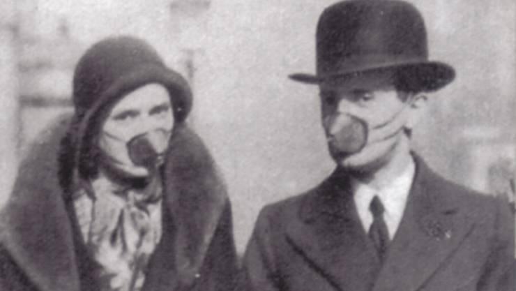 Anfänglich schützen sich die Leute mit Gesichtsmasken gegen die Spanische Grippe.