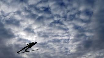 Simon Ammann fliegt durch die bedrohlich anmutenden Wolken Insbrucks.
