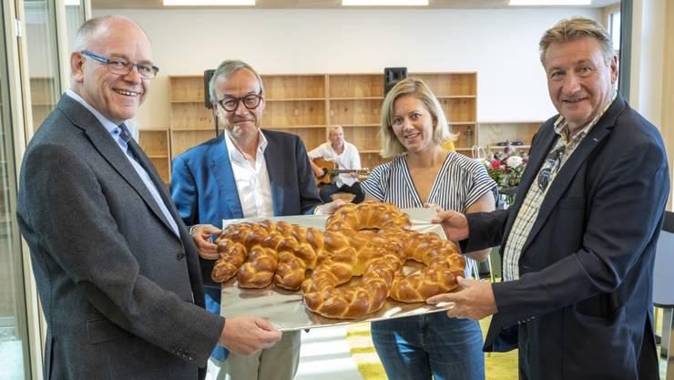 Schulleiter René Keller, Gemeindeammann Fabian Keller, Architektin Sabine Herzog und Gemeindeschreiber Stefan Gloor (v. l.) halten den Brot-Schlüssel.