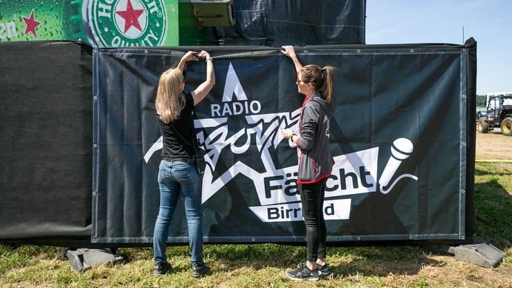 Nicole und Angela vom Argoiva-Team hängen Sponsorenplakate auf