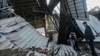 Männer untersuchen die Schäden in einer Werkstatt. Israelische Kampfflugzeuge haben in der Nacht zum Samstag Stellungen der islamistischen Hamas im Gazastreifen angegriffen. Foto: Mohammed Talatene/dpa