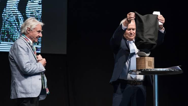 Emil Steinberger wird auf der Eventbühne an der Zentralschweizer Frühlingsmesse Luga der Anerkennungspreis des Kantons Luzern verliehen. Regierungsrat Paul Winiker enthüllt das Kunstobjekt, das Teil des Anerkennungspreises ist.