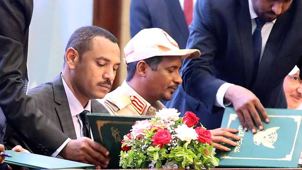 General Mohammed Hamdan Daglo und Achmed al-Rabie von der Allianz für Freiheit und Wandel am Samstag in Khartum beim Unterzeichnen einer Vereinbarung über eine gemeinsame Übergangsregierung.