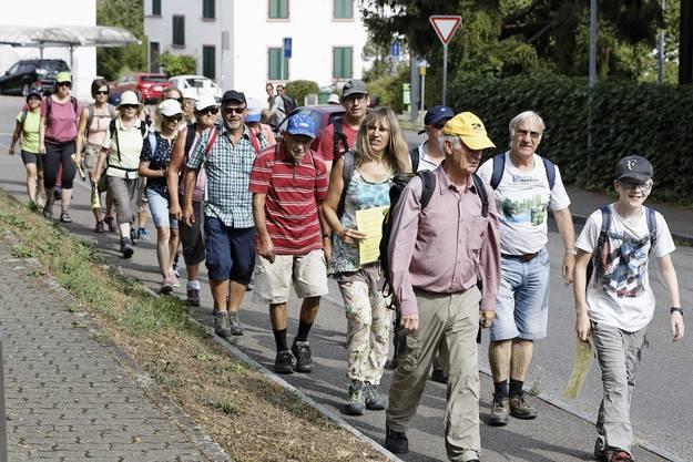 Die 55 Teilnehmerinnen und Teilnehmer setzen sich in Bewegung, allen voraus Wanderleiter Karl Meyer vom Verein Wanderwege beider Basel.