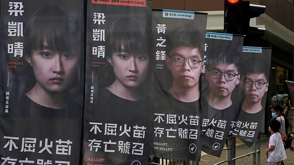 ARCHIV - Der prominente Aktivist Joshua Wong (auf den hinteren drei Bannern zu sehen) sitzt wegen des Vorwurfs der illegalen Organisation eines Protests im Gefängnis. Foto: Kin Cheung/AP/dpa