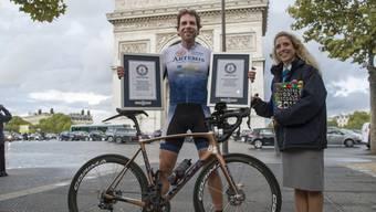 Mark Beaumont am Montag vor dem Triumphbogen in Paris, zusammen mit einer Mitarbeiterin des Guinnessbuchs der Rekorde.