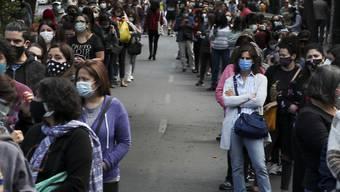 In langen Schlangen warten die Menschen in Chiles Hauptstadt Santiago darauf, ihre Stimmen abzugeben. Foto: Esteban Felix/AP/dpa