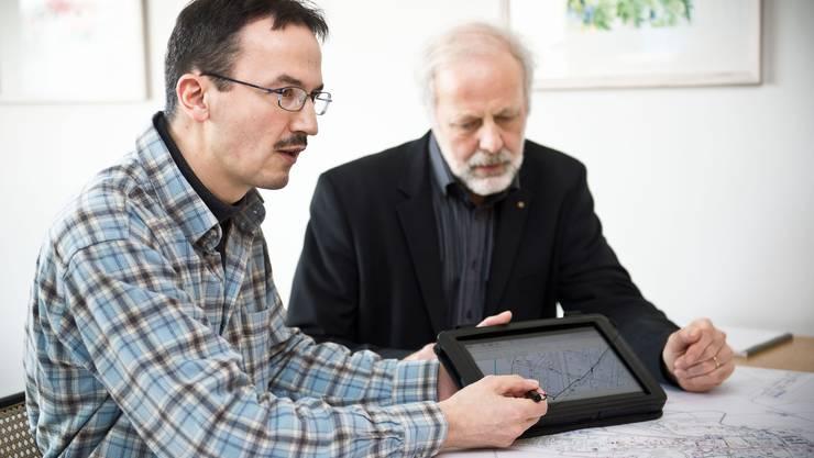 Projektleiter Pius Roth (links) und Beat Steinmann erklären mit der Karte auf dem Tabletcomputer und des Ortsplanes, wie die Haustüren vermessen werden.